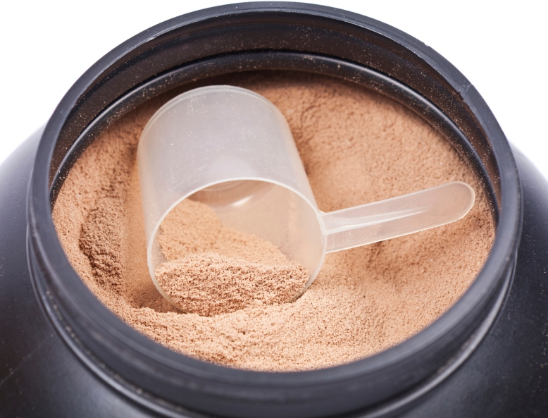 Scoop of chocolate whey isolate protein in black plastic containter
